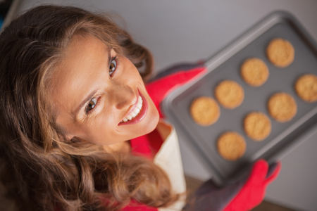 Portrait of smiling young housewife holding pan with christmas cookies Stock Photo - 23533221