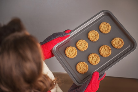 Closeup on pan with christmas cookies in hand of young housewife Stock Photo - 23533290