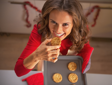 Smiling young housewife tasting cookie from pan with christmas cookies Stock Photo - 23533291