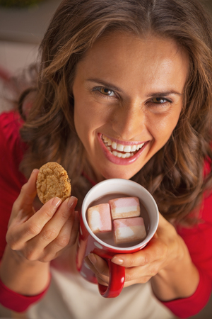 Happy young housewife drinking hot chocolate and eating christmas cookie Stock Photo - 23533293