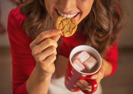 Closeup on happy young housewife drinking hot chocolate and eating christmas cookie photo