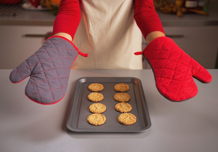 Closeup on kitchen gloves showing by young housewife and christmas cookies on pan Stock Photo - 23533295