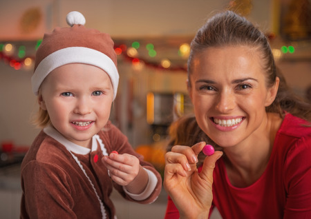 Portrait of smiling mother and baby showing colorful candies in christmas decorated kitchen Stock Photo - 23533303