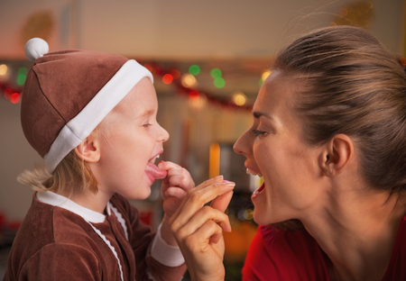 Portrait of smiling mother and baby eating colorful candies in christmas decorated kitchen Stock Photo - 23533304