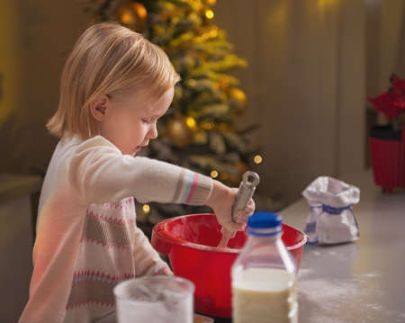 Baby kneading dough in christmas decorated kitchen Stock Photo - 23533305