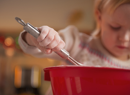 Closeup on baby kneading dough using whisk Stock Photo - 23533306
