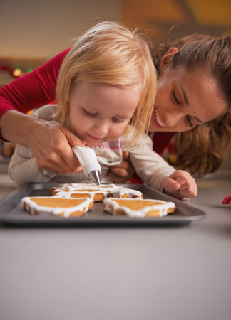 Mother and baby decorating homemade christmas cookies with glaze Stock Photo - 23533307