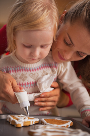 Mother and baby decorating homemade christmas cookies with glaze Stock Photo - 23533309
