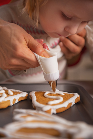 Closeup on mother and baby decorating homemade christmas cookies with glaze Stock Photo - 23533497