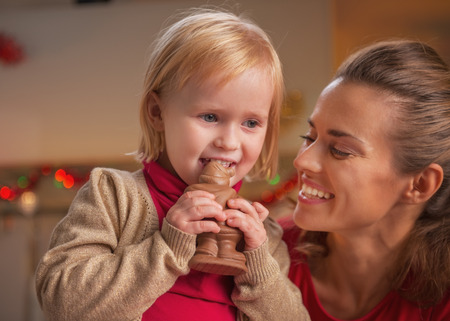 Happy mother and baby eating chocolate santa Stock Photo - 23533499