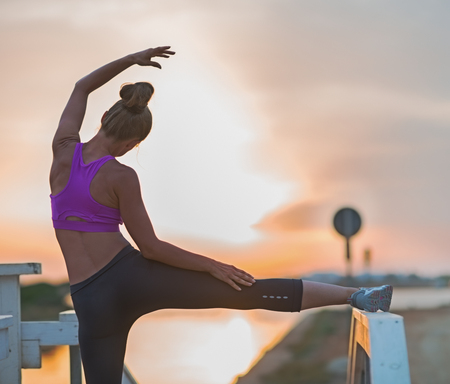 Healthy young woman stretching outdoors in the evening . rear view Stock Photo - 23537187