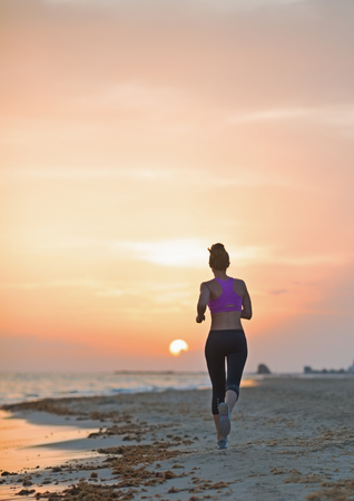 Fitness young woman running on beach in the evening . rear view Stock Photo - 23537191