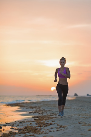 Fitness young woman running on beach in the evening Stock Photo - 23537192