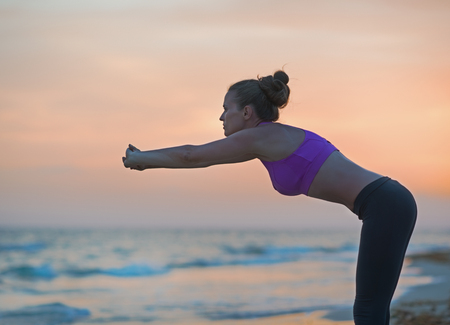 Fitness young woman stretching on beach in the evening Stock Photo - 23537193