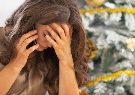 holiday stress: Portrait of stressed woman in front of christmas tree Stock Photo