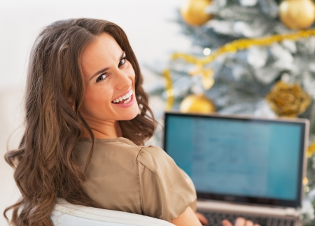 Portrait of happy young woman using laptop near christmas tree Stock Photo - 23746143
