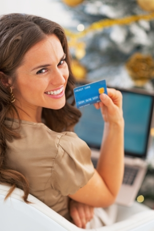 Portrait of smiling young woman with credit card using laptop in front of christmas tree Stock Photo - 23728420