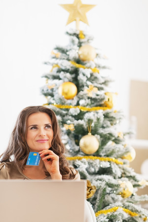Happy young woman with credit card and laptop near christmas tree looking on copy space Stock Photo - 23728422