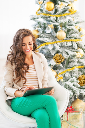 Happy young woman using tablet pc near christmas tree photo