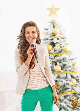 Happy young woman singing in front of christmas tree photo
