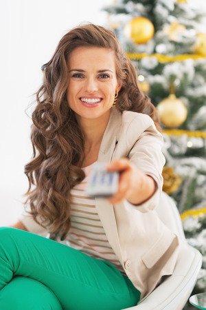tv remote: Portrait of happy young woman with tv remote control in front of christmas tree Stock Photo