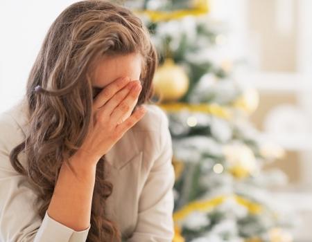 persona deprimida: Subray� joven delante del �rbol de navidad Foto de archivo