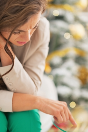 Stressed young woman in front of christmas tree photo