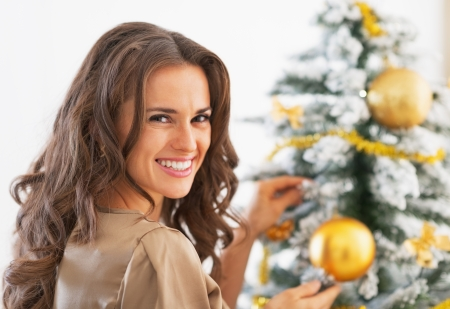 decorating christmas tree: Portrait of happy young woman decorating christmas tree with christmas ball