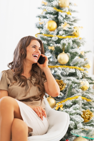 Portrait of happy young woman talking cell phone while sitting near christmas tree Stock Photo - 23728506