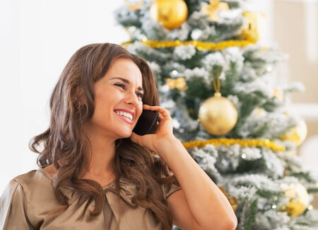 Portrait of happy young woman talking cell phone near christmas tree Stock Photo - 23728508