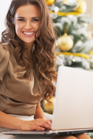 Portrait of smiling young woman using laptop near christmas tree Stock Photo - 23728512