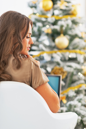 Portrait of thoughtful young woman with laptop in front of christmas tree Stock Photo - 23728515
