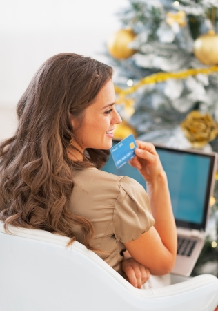 Portrait of thoughtful young woman with credit card and laptop in front of christmas tree Stock Photo - 23728517