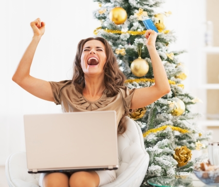 Happy young woman with credit card and laptop rejoicing Stock Photo - 23728523