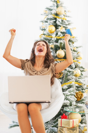 Happy young woman with credit card and laptop rejoicing Stock Photo - 23728524