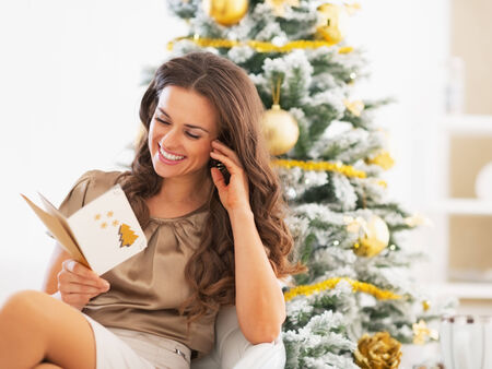 Smiling young woman reading christmas postcard near christmas tree photo