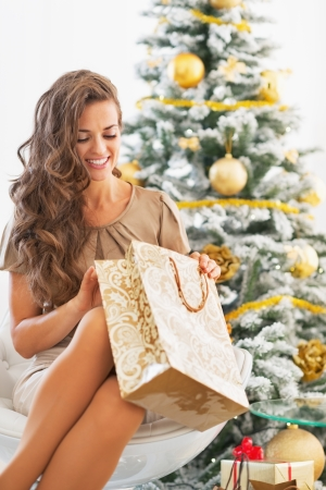 Happy young woman looking into shopping bag near christmas tree Stock Photo