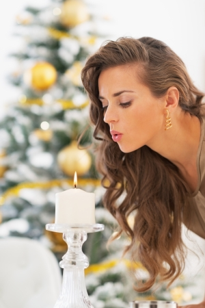 Young woman blowing out candle in front of christmas tree photo
