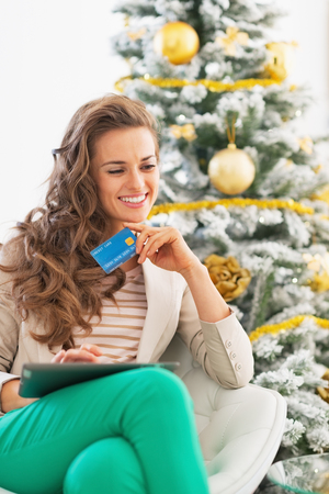 Happy young woman with credit card and tablet pc near christmas tree photo