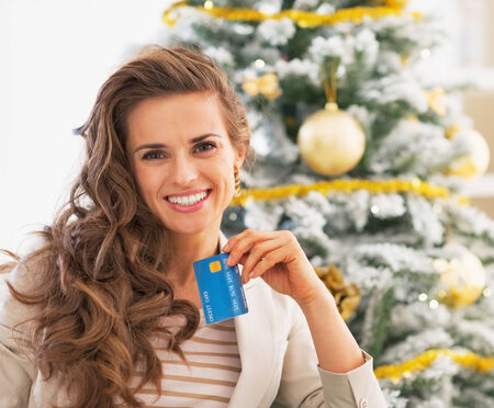 Portrait of happy young woman with credit card in front of christmas tree Stock Photo - 23728597