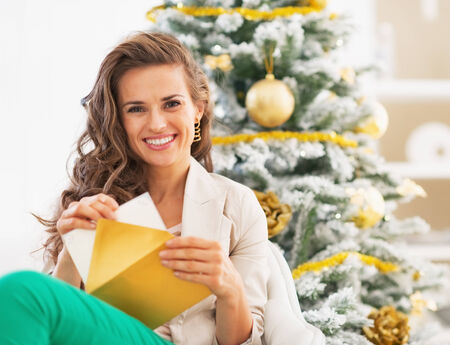 Happy young woman putting postcard into envelope near christmas tree photo