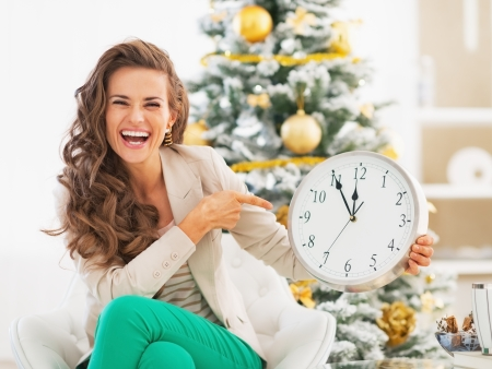 Happy young woman pointing on clock in front of christmas tree photo