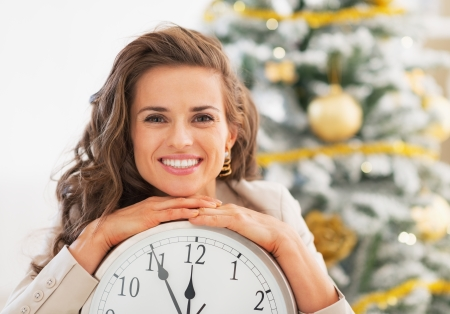 Portrait of smiling young woman showing clock in front of christmas tree photo