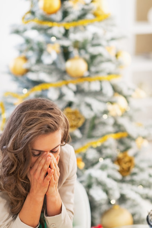 Stressed young woman sitting in front of christmas tree photo
