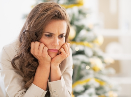 Portrait of frustrated young woman near christmas tree photo