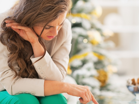 stressful: Stressed young woman in front of christmas tree