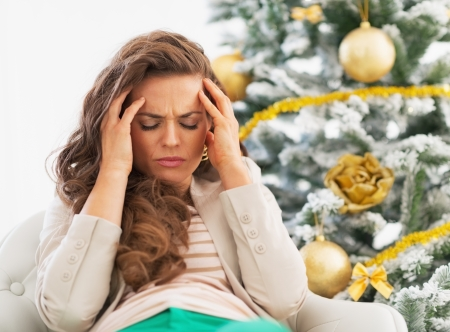 holiday stress: Portrait of frustrated young woman near christmas tree Stock Photo