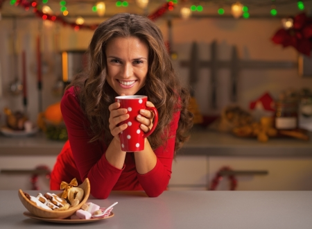 Young woman having christmas cookies in kitchen photo