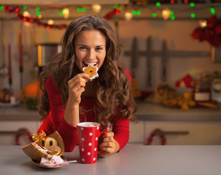 Happy young woman having eating christmas cookies in kitchen photo