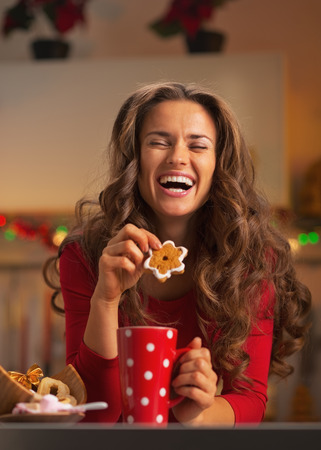 Happy young woman enjoying christmas snacks in kitchen photo